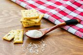 Crispy Salted Crackers, Wooden Spoon With Salt Crystalls, Paper Bag Full Of Crackers On A Red Napkin poster