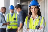 Portrait of woman engineer at building site looking at camera with copy space. Mature construction m poster