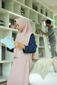 Pretty Young Asian Muslim Woman Enjoying Reading A Book At Reading Room In Casual Clothing, Reading  poster