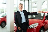 Mature single man with red auto in light car dealership, he is obviously buying a car or is a car de