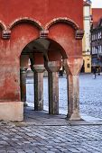 Stone Columns Of Arcades Of Historic Tenement Houses On The Market Square In Poznan poster