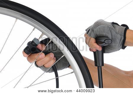 Closeup of a cyclists hands attaching an air pump to the stem of his inner tube, Horizontal format on a white background.