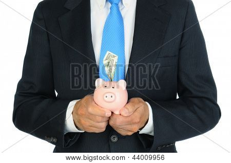 Closeup of a businessman holding a pink piggy bank with a dollar bill stuffed in the slot in front of his body. Hands and torso only, man is unrecognizable. Horizontal format over a white background.