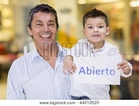 Latin man with his son holding an open sign