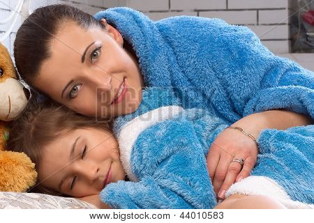 Mom and daughter in the same terry robes lie in bed
