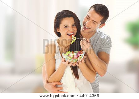 Happy Couple Eating Salad Together In The Kitchen
