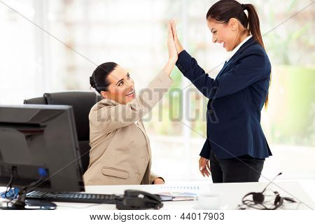 happy young business women doing high five in office