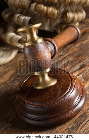 Judge's wig and his gavel on wooden block