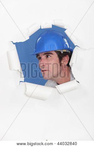 Architect peering through hole
