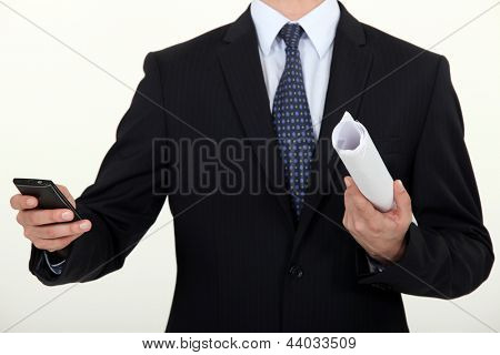 Businessman writing a message on a phone