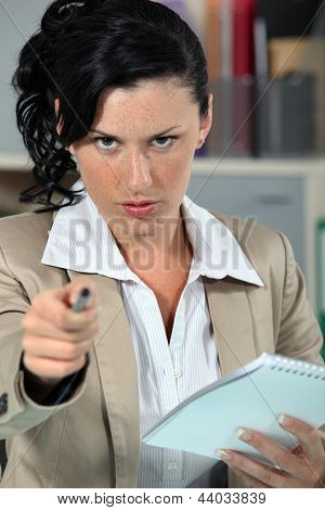 Stern woman pointing pen