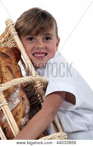 a little girl hugging a wickerwork bread bin full of bread