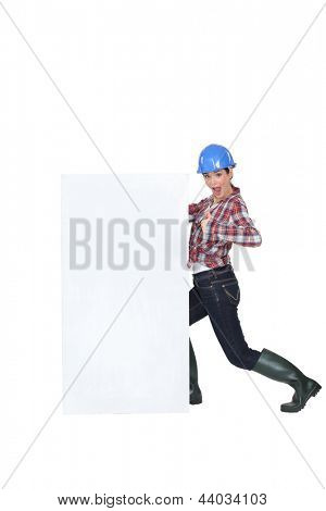 Construction worker by a billboard.