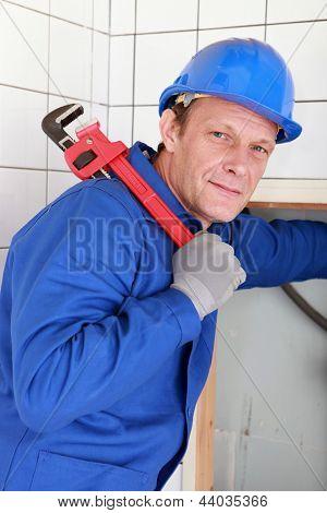 Canalizador com uma chave grande vermelha realizada por cima do ombro