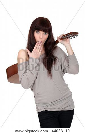 Woman stood holding acoustic guitar