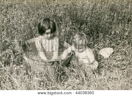 Vintage photo of little girls bathing in washtub (early eighties)