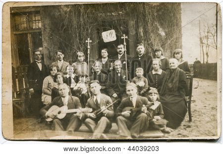 KALISZ, POLAND,CIRCA 1935: group of unidentified people, men, women, children pose for a photo. An elderly couple holds crosses, some men musical instruments. Perhaps it is a 50th wedding anniversary. circa 1935 in Kalisz, Poland