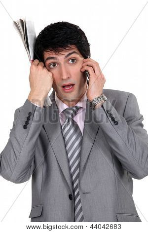 young elegant businessman holding newspaper makes a call