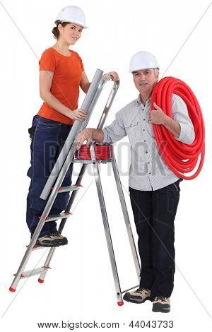 female plumber on ladder with male tutor