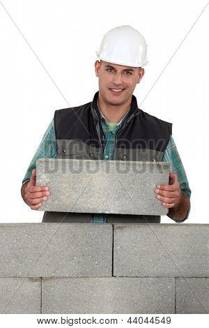Tradesman placing a stone