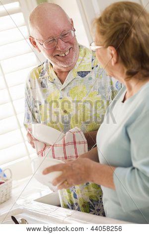 Casal adulto sênior tendo divertida lavar pratos juntos dentro da cozinha de sua casa.