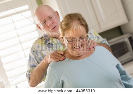 Happy Senior Adult Husband Giving Wife a Shoulder Rub in the Kitchen.