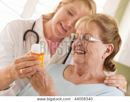 Happy Female Doctor or Nurse Explaining Prescription to Senior Adult Woman.