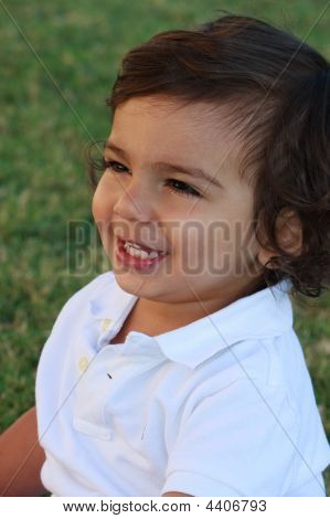 Boy Sitting In Grass Smiling