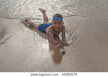 Playful Boy On The Beach With Sea  On Background.