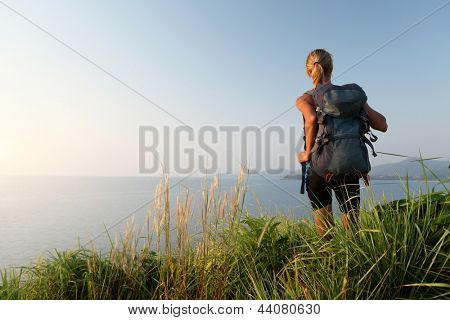 Hiker with backpack relaxing on a green meadow and enjoying sunset