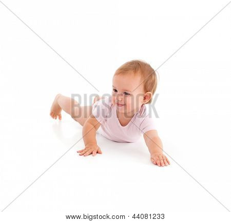 Impish little girl rolling on floor, having fun.