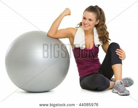 Smiling Fitness Young Woman Sitting Near Fitness Ball And Showin