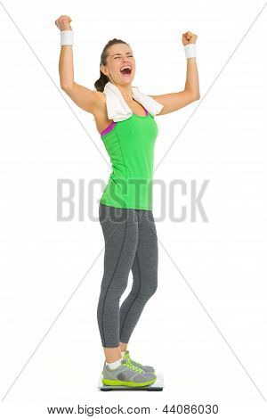 Happy Fitness Young Woman Standing On Scales And Rejoicing Success