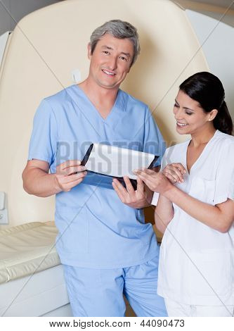 Portrait of male radiologic technician with female colleague holding clipboard while standing by MRI scan machine