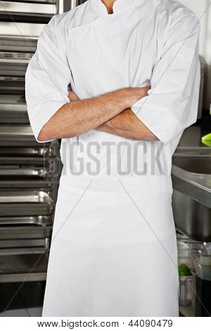 Midsection of young male chef standing with arms crossed