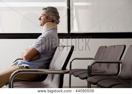 Side view of mature man with neck brace waiting in hospital lobby