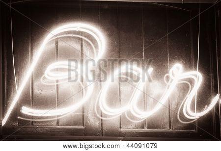 """Glowing """" Bar """" sign at night"""