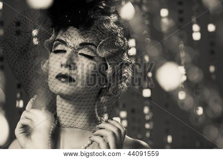 Monochrome portrait of elegant blond retro woman with beautiful hairdo wearing veil