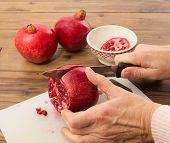 Hands cutting a pomegranate in four quarters