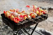 stock photo of kababs  - chicken shish kebab on bbq grill in sauce on skewers with tomatoes and peppers - JPG