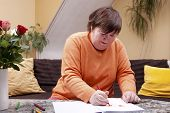 picture of physically handicapped  - Disabled woman painted with colored pencils in a book - JPG