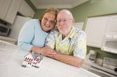 picture of over counter  - Happy Senior Adult Couple Gazing Over Small Model Home on Their Kitchen Counter - JPG