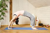 image of dhanurasana  - An image of a pretty woman doing yoga at home  - JPG