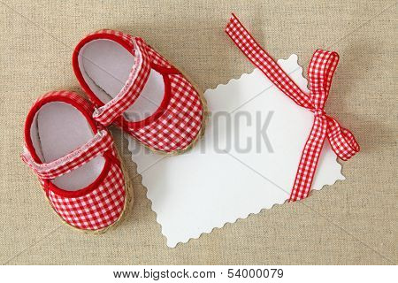 Red shoes and blank note on brown background