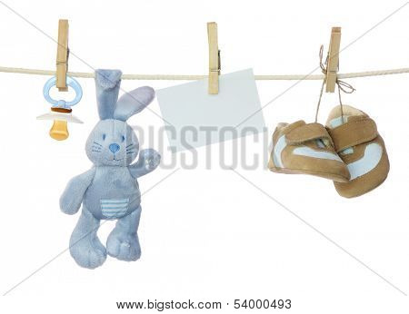 Blue baby goods and blank note hanging on the clothesline