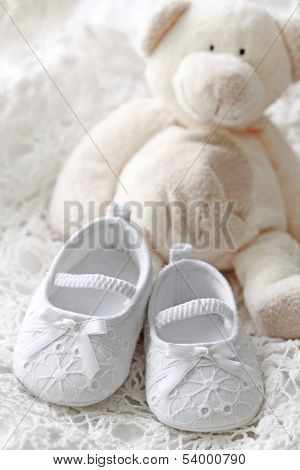 Baby girl shoes and teddy bear on white background