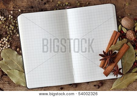 Blank notebook with spices on wooden background