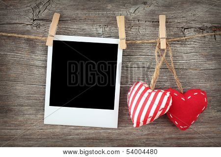 Two red hearts and blank instant photo on clothespin