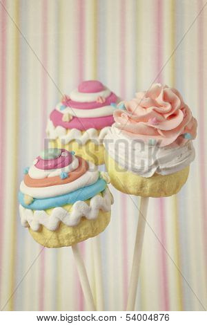 Colorful cupcake pops on striped background