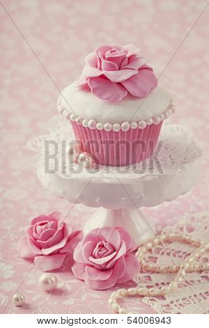 Cupcake with rose flower on a stand